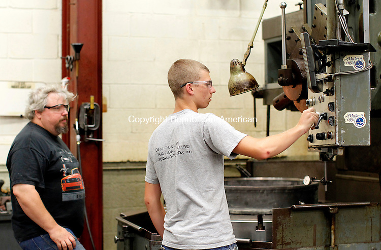 Barkhamstead, CT- 21, July 2010-072110CM10  Glen Derby, an employee at Sterling Engineering helps Jonathan Sedgwick, a graduate of Oliver Wolcott Tech High School, with a machine.  Sedgwick was hired with the company after completing an internship there.     --Christopher Massa Republican-American