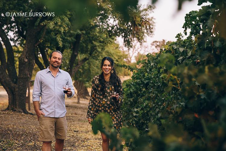 Couple walking through a California vineyard.