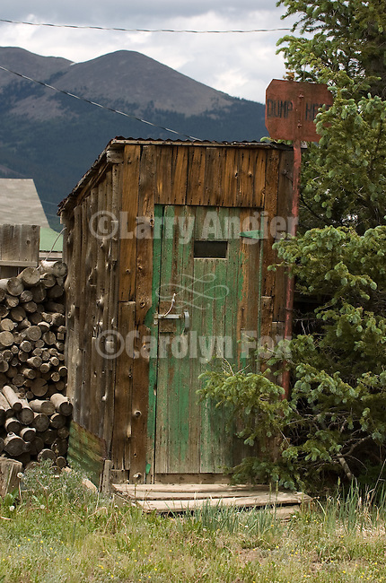 Wooden outhouse with green door and wood pile, Colorado Rockys
