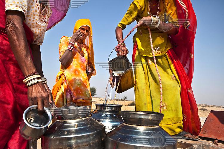 Women collecting water from concrete Taankas, underground rainwater harvesting tanks, built in the Thar Desert near Phalodi..