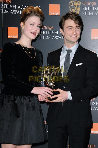 Holliday Grainger and Daniel Radcliffe.Orange British Academy Film Awards Nominations announcement, London, England..January 17th, 2012.BAFTA BAFTAs half length suit black grey gray tie top skirt trophy award.CAP/CJ.©Chris Joseph/Capital Pictures.