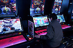Person playing Lord of Vermilion card game arcade slot machines in Tokyo, Japan