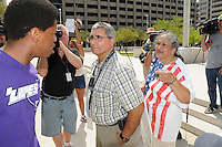 Phoenix, Arizona. July 24, 2012 - Jarvis Johnson (left) and Martha Payan (right) hold a heated verbal argument over Sheriff Arpaio outside the Sandra Day O'Connor United States Federal Courthouse in Phoenix, Arizona as Arpaio testifies in court. Detective Al Ramirez (center) watches. Maricopa County Sheriff Joe Arpaio testified in court on July 24, 2012 to respond to accusations his office (MCSO) has been racial profiling Latinos as they enforce local immigration laws in the county. The lawsuit is known as Ortega-Melendres vs. Arpaio. Photo by Eduardo Barraza © 2012