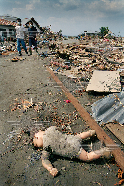 Survivors looking for missing relatives in the Ulele district come across a child's doll amidst the devastation following the tsunami which struck South Asia on 26/12/2004..An underwater earthquake measuring 9 on the Richter scale triggered a series of tidal waves which caused devastation when they struck dry land. 12 countries were affected by the tsunami, with a combined death toll of over 280,000. Aceh, the closest landfall to the epicentre of the quake, suffered the greatest loss of life.
