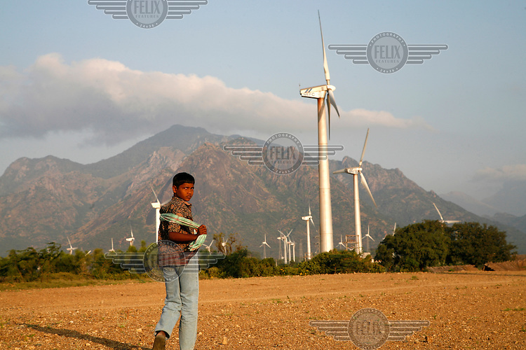 A young boy walks past the turbines at Muppandal wind farm. Muppandal is one of the largest wind farms in Asia.