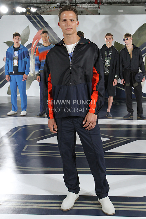 Model Nathaniel poses in a blocked nylon anorak in navy, t-shirt in stone, and tech-nylon jogger in navy, from the Perry Ellis Spring 2017 collection by Michael Maccari, on July 11th 2017, during New York Fashion Week Men's Spring Summer 2017.