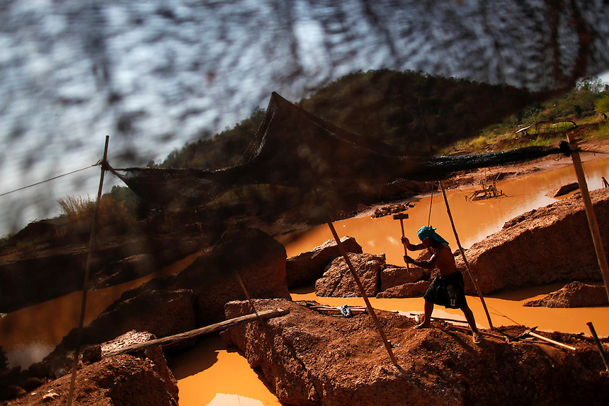 Boonchu Tiengtan breaks stones at a primitive gold mine in Panompa near Phichin February 17, 2011. A group of Thais use primitive tools and methods to extract gold from self-run mines near the countries biggest and most modern Chatree gold mine. A family working at the mine can get around one gram of gold per day they sell at the site for about 1000 Thai bahts (32 USD).   REUTERS/Damir Sagolj (THAILAND)