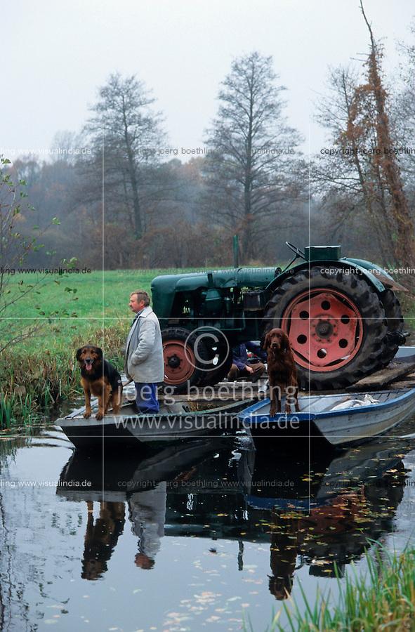 GERMANY, farmer transport old tractor on boat to island field for harvest of horseradish in Spreewald / DEUTSCHLAND, Spreewald, Bauer mit Hund transportiert alten Traktor Famulus auf Kahn zur Ernte von Meerrettich auf einer Insel