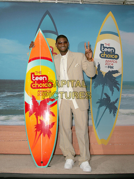 USHER.The 2004 Teen Choice Awards held at The Universal Ampitheatre in Universal City, California.August 8, 2004.full length, sunglasses, shades, v sign, peace sign, gesture, surf board, beige, tan stripe suit.www@capitalpictures.com.sales @capitalpictures.com.©Capital PIctures