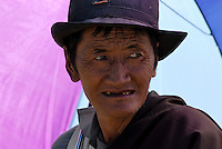 Taken cover under the umbrella during the days heat..Traditional Tibetan dress up in their finest and wearing their most precious Jewelry during this festival. The most common gem stones are worn in the jewelry are Turquoise and red coral..Changtang Chachen Horse Race Festival (August 10th) is the most important festival in northern Tibet during the golden season on the grassland. Thousands of herdsmen throng to Nakchu riding fine horses and carrying local products. They erect a tent city south of Nakchu town. They celebrate with a thrilling horse race, archery contests, and demonstrations of horsemanship. Song-and-dance troupes from all parts of Tibet add to the festivity. It is said that this is the highest horse racing festival in the world, at 4800 meters.