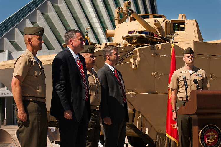 "WASHINGTON, DC - May 4: Col. Keith M. Moore, program manager for Advanced Amphibious Assault, William E. Taylor, of Program Executive Officer Land Systems, Lt. Gen. George J. Flynn, deputy commander for Combat Development and Integration, and U.S. Rep. Rob Wittman, R-Va., stand at attention during the ""Marines' Hymn"" during the ceremony unveiling of the Marines' newest Expeditionary Fighting Vehicle (EFV) prototype. The armored amphibious vehicle is designed carry 17 combatants, plus a three person crew, from Navy ship ""beyond the horizon"" to objectives inland. The ceremony was held at the National Museum of the Marine Corps in Triangle. Va. (Photo by Scott J. Ferrell/Congressional Quarterly)"