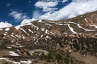 One of the switchbacks along US Highway 6 climbing Loveland Pass lies nesteled in among patches of green,  patches of snow with the typical Colorado  blue skies and puffy clouds above.