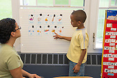 MR / Schenectady, NY. Zoller Elementary School (urban public school). Kindergarten classroom. Paraprofessional (Puerto Rican American) uses vocabulary cards to teach Spanish-language lesson. Boy, 6, African American /  Puerto-Rican American. MR: Pac1, Cas12. ID: AM-gKw. © Ellen B. Senisi.