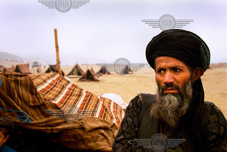 © Tim Dirven / Panos Pictures..Shirim Tagab, near Meymaneh, Afghanistan, December 2001..A man shivers in the cold at the refugee camp of Xjosa Sabz Poosh. 1100 families live in basic tents, and more than 200 people have died from hunger and cold over the past seven months. At night several families crowd together in one tent, even inviting in their donkeys for the extra body heat.