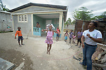 Myriam Pierre helps children jump rope in front of a new house built by Servicio Social de las Iglesis Dominicanas in the Haitian community of Ganthier. Pierre is a program officer for SSID, a member of the ACT Alliance. The organization has worked extensively in the community since it was devastated in 2016 by Hurricane Matthew.<br /> <br /> Parental consent obtained.