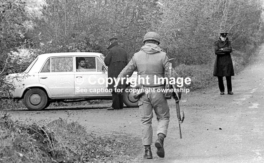 A guard, an Irish policeman, checks out a motorist along the Co Louth-South Armagh border with N Ireland. He is supported by Irish Army soldiers from the 27th Battalion stationed in Dundalk. 197512120773h..Copyright Image from Victor Patterson, 54 Dorchester Park, Belfast, United Kingdom, UK...For my Terms and Conditions of Use go to http://www.victorpatterson.com/Victor_Patterson/Terms_%26_Conditions.html