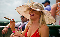 LOUISVILLE, KY - MAY 04: A woman enjoys a cigar on Kentucky Oaks Day at Churchill Downs on May 4, 2018 in Louisville, Kentucky. (Photo by Scott Serio/Eclipse Sportswire/Getty Images)