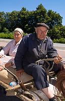 Farming couple riding horse carriage on road from Kiev to Lviv, Ukraine