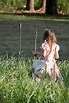 A young girl walking through grass in American historical clothing