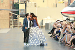 Fashion designer Douglas Hannant walks runway with Aminata Niaria, at the close of the Douglas Hannant Resort 2012 fashion show, on top the USS Intrepid, June 7, 2011.