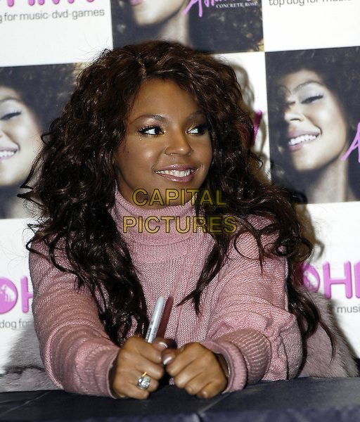 "ASHANTI .Signs copies of her new album, ""Concrete Rose"" at.HMV Trocadero store, London, 22 January 2005..portrait headshot pink polo roll neck top jumper .Ref: HT.www.capitalpictures.com.sales@capitalpictures.com.©Capital Pictures."