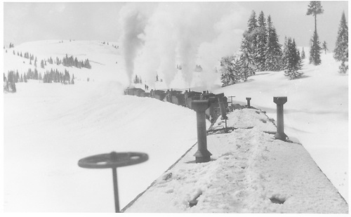 Rotary snowplow pushed by four engines clearing snow on Cumbres Pass.  View is from caboose roof behind outfit cars.<br /> D&amp;RGW  Cumbres Pass, CO