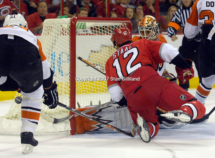 The Carolina Hurricanes' Eric Staal (12) reaches for a puck in the crease defended by the Philadelphia Flyers' Jason Smith (21) and goalie Martin Biron during their game Wednesday, Nov. 21, 2007 in Raleigh, NC. The Flyers won 6-3.