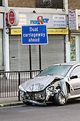 A wrecked car  by a dual carriageway sign on the Harrow Road, West London.