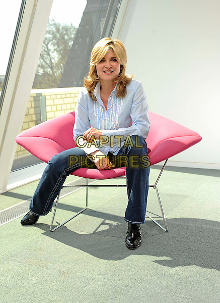 ANTHEA TURNER.Pictured In Central London, England, UK, April 19th 2011..full length jeans sitting down chair studio session  blue shirt pink lips mouth seat .CAP/FIN.©Steve Finn/Capital Pictures.