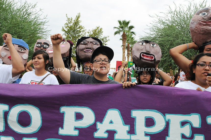 """Phoenix, Arizona (July 28, 2012) - About three hundred people marched to protest the second anniversary of the approval of some provisions of the SB 1070 immigration law. The march, called """"No Papers, No Fear"""" was organized by immigrant rights groups who say the law discriminates people of brown skin. In this photograph, protester and undocumented immigrant Isela Meraz helps hold a banner as the """"No Papers No Fear"""" march begins in Phoenix. Meraz was arrested for a civil disobedience act on July 24 for blocking a major intersection in Downtown Phoenix. Photo by Eduardo Barraza © 2012"""