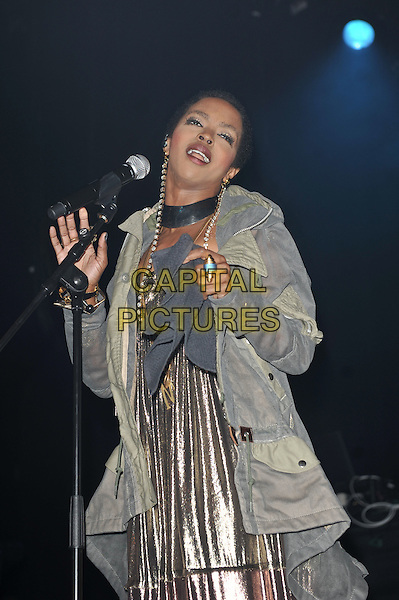 Lauryn Hill .performing live in concert at indigo2, Greenwich, London, England UK, .14th April 2012..music live on stage performing in concert gig half length silver shiny dress jacket coat grey gray anorak necklaces lame  microphone singing mouth open .CAP/MAR.© Martin Harris/Capital Pictures.