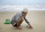 Nguyen Van Dich, who lost his right hand to wartime ordnance, collects shells along the coast near Quang Phu, Vietnam. He supports his family by selling the shells.