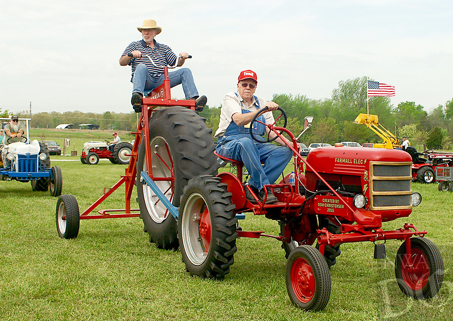 Photo by Randy Moll<br /> Don Christensen of Gentry drives his electric-powered Farmall tractor and pulls a huge tricycle on Friday (April 14, 2017) at the Tired Iron of the Ozarks show in Gentry.