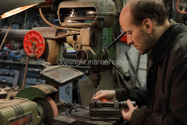 Man clamping a piece of steel and about to drill, in the Soleil Rouge workshop of Nicolas Desbons, metalworker and artist, photographed in 2017, in Montreuil, a suburb of Paris, France. Desbons works mainly in steel but often in conjunction with other materials such as fibreglass, glass and clay, using both cold metal and forge techniques. He produces both figurative and abstract sculptures as well as furniture and lighting. Picture by Manuel Cohen
