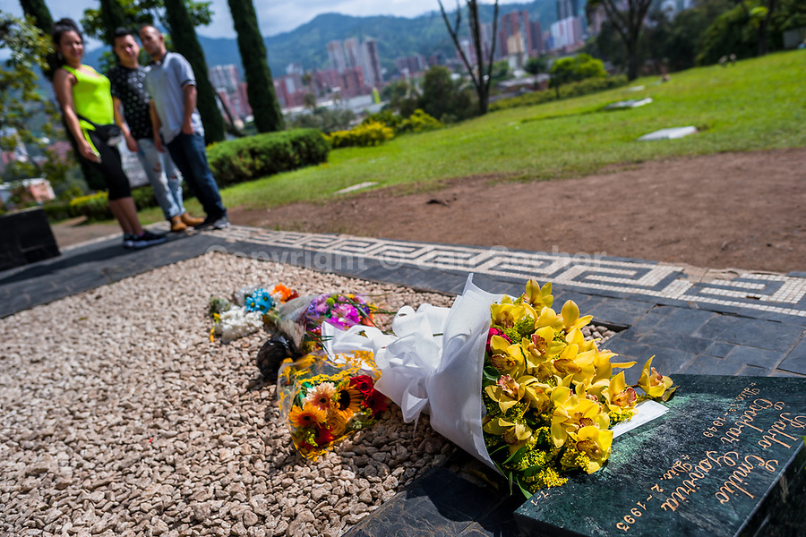 """Colombian visitors gather around the tomb of the drug lord Pablo Escobar at the cemetery of Montesacro, in Itagüí, Colombia, 2 December 2017. Twenty five years after Pablo Escobar's death, the legacy of the Medellín Cartel leader is alive and flourishing. Although many Colombians who lived through the decades of drug wars, assassinations, kidnappings, reject Pablo Escobar's cult and his celebrity status, there is a significant number of Colombians who admire him, worshipping the questionable """"Robin Hood"""" image he had. Moreover, in the recent years, the popular """"Narcos"""" TV series has inspired thousands of tourists to visit Medellín, creating a booming business for many but causing a controversial rise of narco-tourism."""
