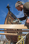 Port Townsend, Boat Haven Marina, shipwright, Ben Feldman, Cunningham Ships Carpentry, planing a wooden plank for the Bristol Bay monkey boat Snug, Port of Port Townsend, Jefferson County, Olympic Peninsula, Puget Sound, Washington State, Pacific Northwest, USA,