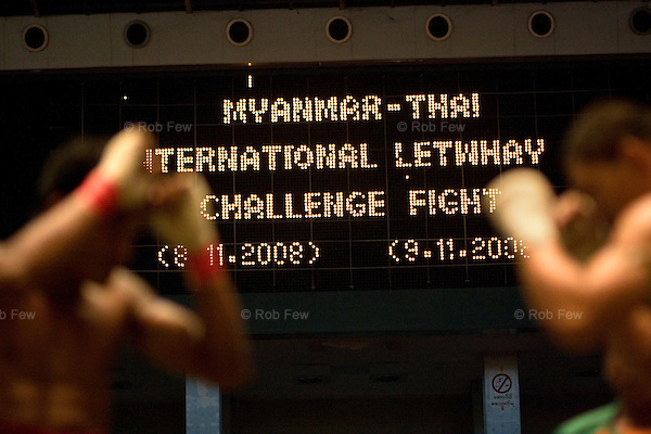 In November 2008, Yangon played host to the first ever international boxing match held in Burma. Thai boxers came for a two-day fight in Yangon's central stadium - a grueling event and a litmus test for future international sporting events in the closed-off country.<br /> <br /> Here, a Burmese and a Thai fighter square off at the start of their bout. Since this is Burmese style boxing, there are no gloves.