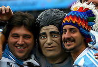 Argentina supporters pose with a fan wearing a Diego Maradona mask