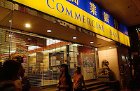 People pass Asia Commercial Bank in Hong Kong..