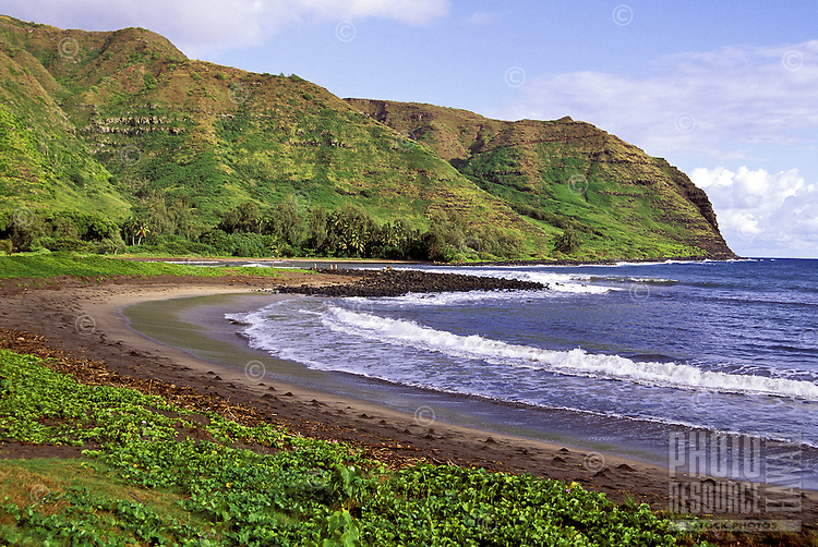 A beautiful secluded Molokai beach and rugged coastline with lush green mountains in the background.