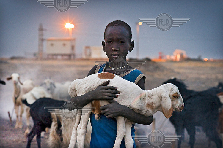 Boy holding his kid goat near an oil pumping station. Many animals have died after drinking polluted water in the area.
