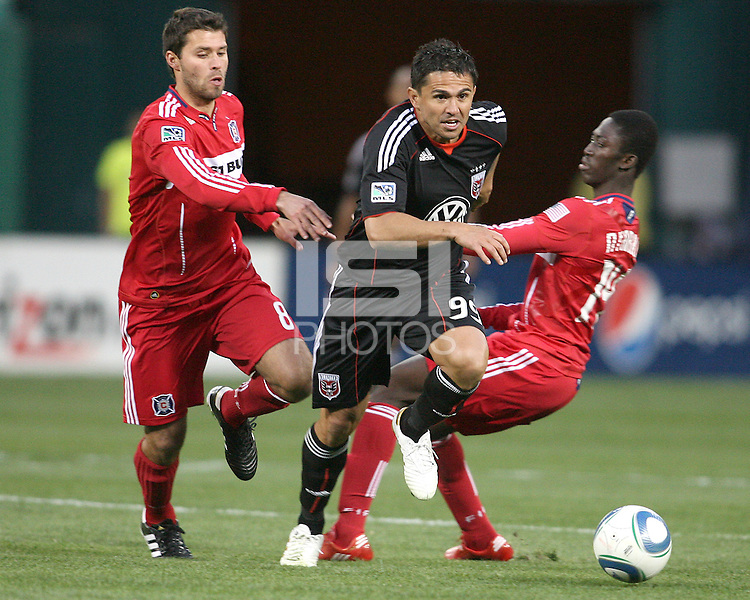 Jaime Moreno #99 of D.C. United bursts past Peter Lowry #8 and Patrick Nyarko #14  of the Chicago Fire during an MLS match on April 17 2010, at RFK Stadium in Washington D.C. Fire won the match 2-0.
