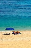 Couple sunbathing on the famous Turquoise waters of Myrtos Beach (??????? ??????), Kefalonia, Greek Ionian Islands