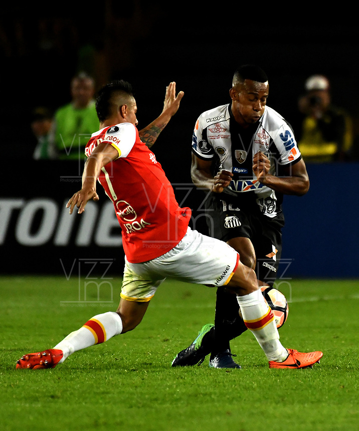 BOGOTA - COLOMBIA – 19 – 04 - 2017: Juan Roa (Izq.) jugador de Independiente Santa Fe, disputa el balon con Jonathan Copete (Der.) jugador de Santos, durante partido entre Independiente Santa Fe de Colombia y Santos de Brasil, de la fase de grupos, grupo 2, fecha 3 por la Copa Conmebol Libertadores Bridgestone 2017, en el estadio Nemesio Camacho El Campin, de la ciudad de Bogota. / Juan Roa (L) player of Independiente Santa Fe, fights for the ball with Jonathan Copete (R) player of Santos during a match between Independiente Santa Fe of Colombia and Santos of Brasil, of the group stage, group 2 of the date 3, for the Conmebol Copa Libertadores Bridgestone 2017 at the Nemesio Camacho El Campin in Bogota city. VizzorImage / Luis Ramirez / Staff.