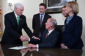 Director of National Intelligence Dan Coats (C), with his wife Marsha Coats (R) and family members, shakes hands with United States Vice President Mike Pence (L)during a swearing in ceremony in the US Capitol in Washington, DC, USA, 16 March 2017.<br /> Credit: Shawn Thew / Pool via CNP