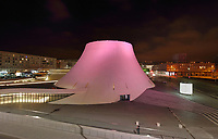 Le Volcan or the Volcano at night, illuminated in pink, auditorium opened 1982, designed by Oscar Niemeyer, 1907-2012, and Jean-Maur Lyonnet, at the Maison de la Culture du Havre, Le Havre, Normandy, France. Behind are apartment buildings designed by Auguste Perret, 1874-1954, who led the reconstruction of Le Havre in the 1950s, after the town was completely destroyed in WWII. The large volcano shown here contains a 1200 seat theatre and 350 seat cinema, while the small volcano (behind, left) has a 500 seat hall and 80 seat auditorium and is now used as a reference library. The forum is built from concrete and the buildings are linked and accessed via ramps. The centre of Le Havre is listed as a UNESCO World Heritage Site. Picture by Manuel Cohen