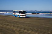 A tourist bus heads up Ninety Beach towards Cape Reinga. Tauroa Peninsula is in the distance. Far North. Northland, New Zealand.