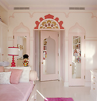 A girl's bedroom has been designed in an Indian theme in pink and white with a stained-glass fanlight above the mirrored door