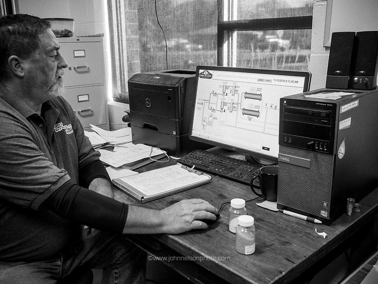 Bill England, backflow technician at Lake Station's water filtration plant,  looks at the schematic for the water system. He works for Utility Services, which was hired by the city to run the plant.