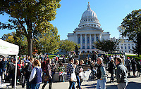 People walk in front of the Wisconsin State Capitol Building at the Dane County Farmers' Market on Saturday, October 17, 2015 in Madison, Wisconsin